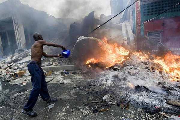 Man attempting to douse a fire Port-au-Prince after the 2010 earthquake